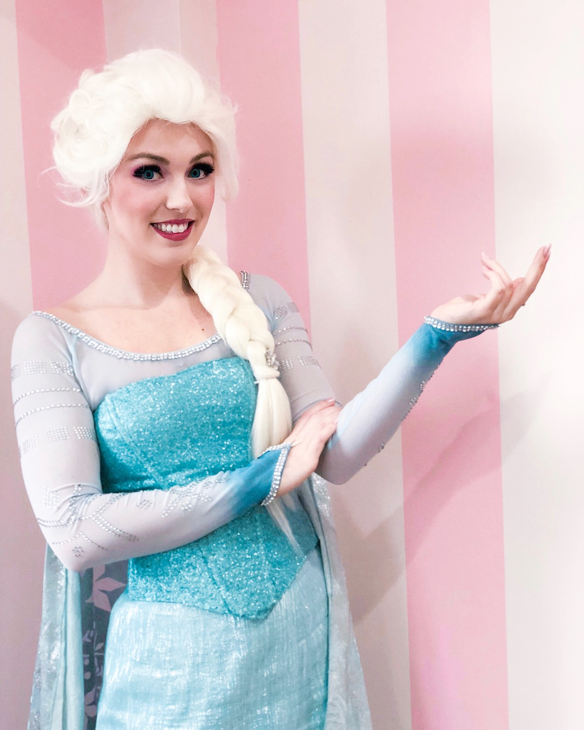 Elsa is smiling and ready to make a flurry with her iconic ice hand pose