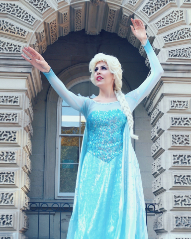 Elsa has her hands raised and looking toward the Frozen flurry she's about to create