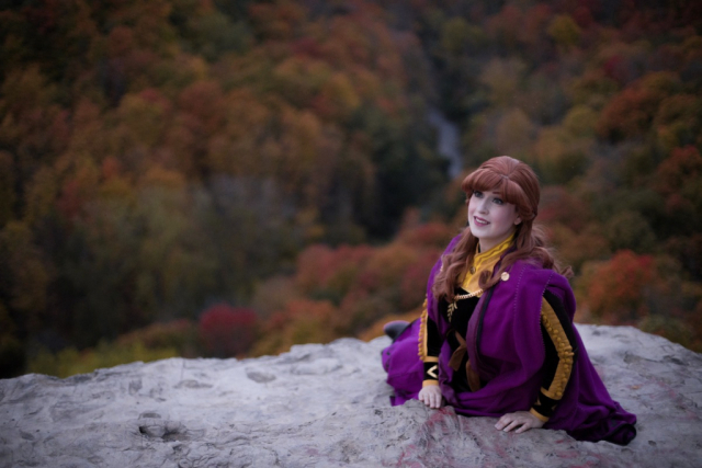 Anna is sitting on a cliff which overlooks the enchanted forest and smiling