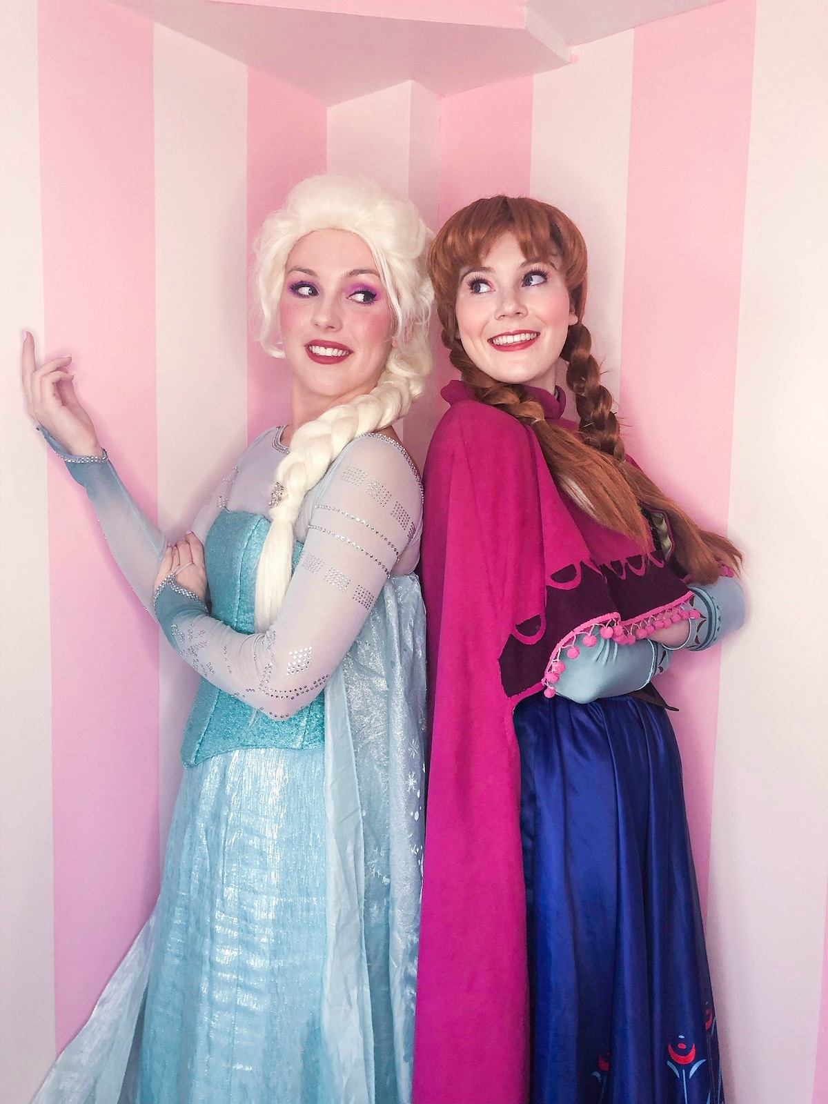 Elsa and Anna are smiling and looking at each other
