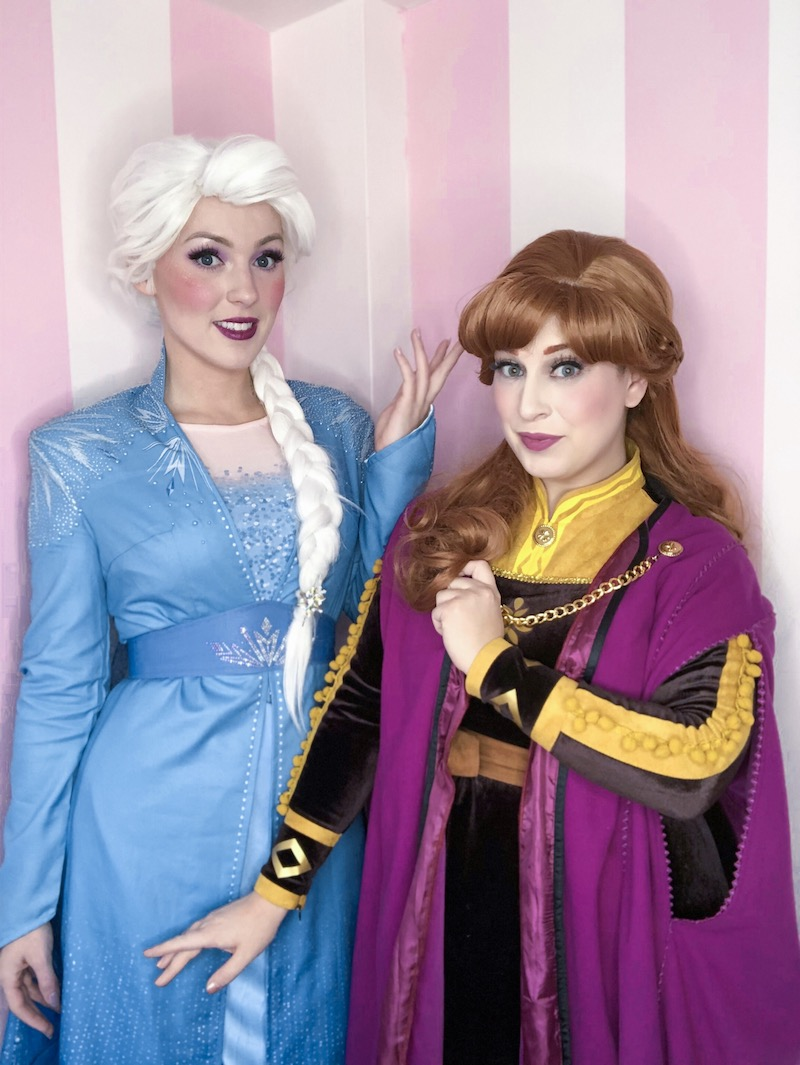 Anna and Elsa are posing in their new Frozen 2 costumes